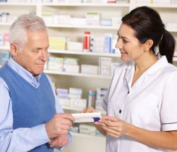 pharmacist assisting senior man in pharmacy